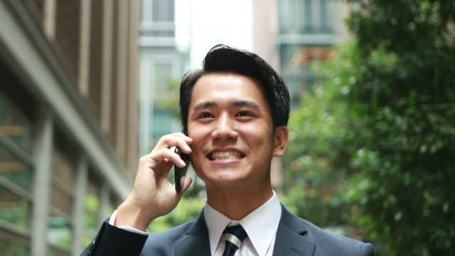felice giovane uomo d'affari che parla al telefono in asia - ear talking video stock e b–roll