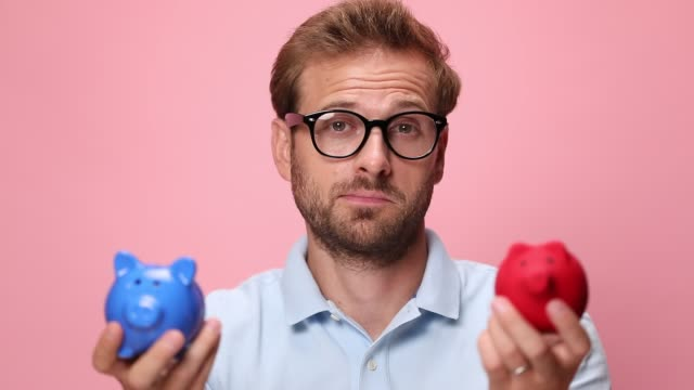 happy young casual guy in blue polo shirt holding piggy banks and analysing, rising eyebrows in a clueless manner and having no idea on pink background