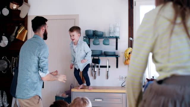 Happy young Caucasian father catching cheerful little son jumping in his arms, family fun time in kitchen slow motion. video