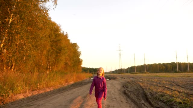 Happy young caucasian girl jumping by country road. White caucasian girl happy laughing. video