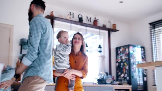 glückliche junge kaukasische mutter und vater spielen mit niedlichen kleinen söhnen in hausküche, familienspaß konzept zeitlupe. - reliability stock-videos und b-roll-filmmaterial