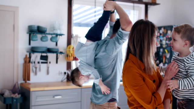 Happy young Caucasian mother and father playing with two little sons in the kitchen, family fun time at home slow motion