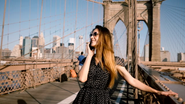 Happy young Caucasian woman in vintage sunglasses talking on the phone, hair blowing in the wind at Brooklyn Bridge 4K