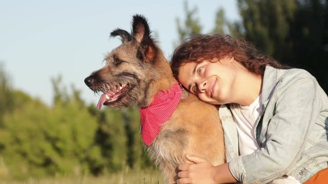 Happy young caucasian woman with her dog at the park at the summertime.