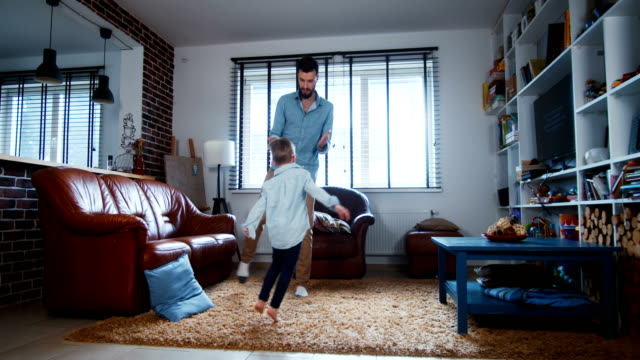 Happy young cheerful Caucasian father and little son have fun dancing together in modern house living room slow motion. video