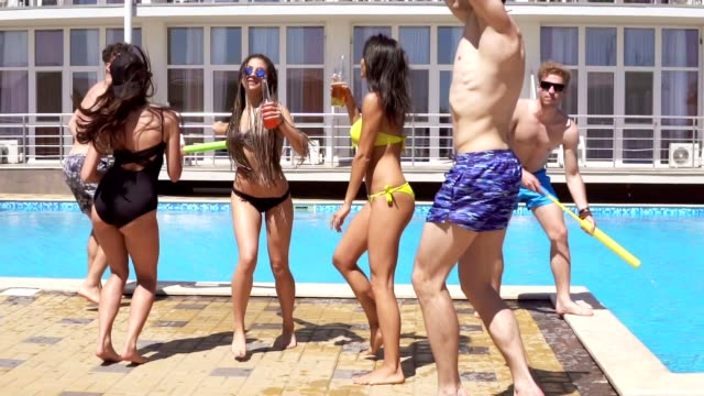 happy young cheerful friends dancing and having fun at the pool. summertime pool party. slowmotion shot - bachelor party stock videos and b-roll footage