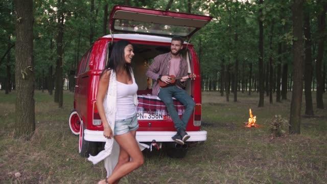 glückliche junge fröhlich zeitlupe gemischt rennen paar, ein bisschen spaß im wald in der nähe von retro hippie-kleinbus, - van stock-videos und b-roll-filmmaterial