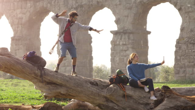 Happy young couple backpackers tourists on a log trunk taking selfies photos with smartphone in front of ancient roman aqueduct ruins in romantic parco degli acquedotti park in rome at misty sunrise slow motion TRIPOD video