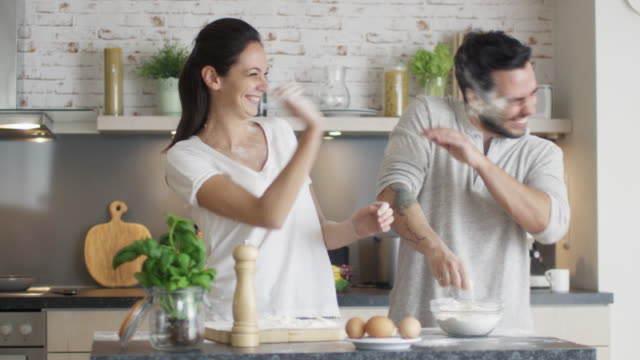Happy Young Couple Cooks in the Kitchet. As a Joke They Started Throwing Flour at Each Other. Then Smilingly Embrace. Happy Young Couple Cooks in the Kitchet. As a Joke They Started Throwing Flour at Each Other. Then Smilingly Embrace. Shot on RED Cinema Camera in 4K (UHD). young couple stock videos & royalty-free footage
