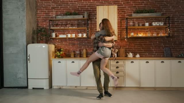 stockvideo's en b-roll-footage met gelukkig jong paar danst in de keuken. - interior design
