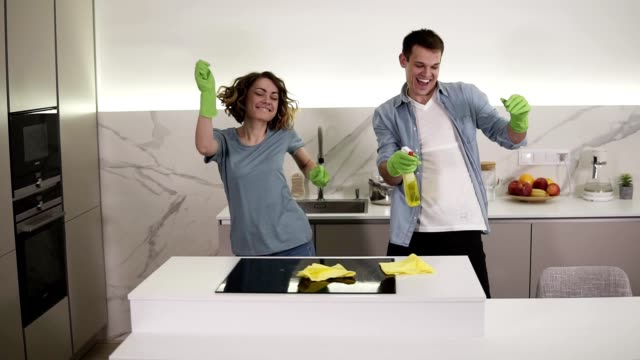 Happy young couple dancing in kitchen both in green rubber gloves having fun on clean-up day in studio apartment. Modern youth, people and housekeeping concept video