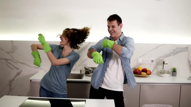 Happy young couple dancing synchronously in kitchen both in green rubber gloves having fun on clean-up day in studio apartment. Funny moves. Modern youth, people and housekeeping concept video