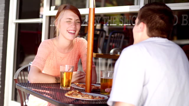 Happy young couple eat pizza and beer video