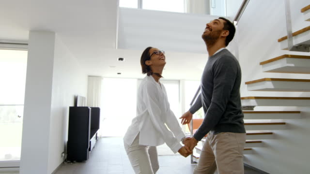 Happy Young Couple Enters Their Newly Purchased Home, They're Full of Wonderment. House is Bright, Has Floor to Ceiling Windows and Seaside View.