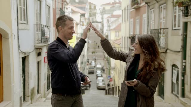happy young couple giving high five outdoors. - cinque oggetti video stock e b–roll