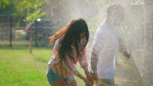 happy young couple has fun on a hot summer day playing with water hose sprinkler in the garden. two young people in love got wet jokingly fighting with hose. in slow motion. - tubo flessibile video stock e b–roll