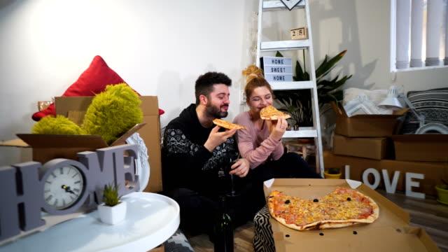 glada unga par har en pizza lunch break på golvet efter att ha flyttat till ett nytt hem med lådor runt dem - flyttlådor bildbanksvideor och videomaterial från bakom kulisserna