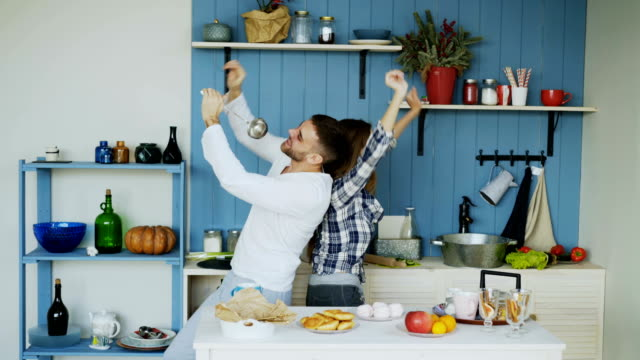 vídeos de stock e filmes b-roll de happy young couple have fun dancing and singing in kitchen while listening to music in the morning at home - utensílio