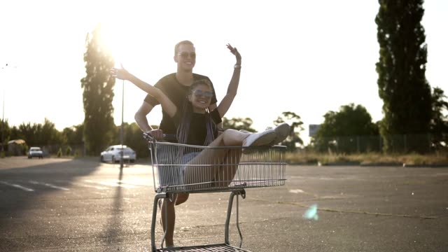 Happy young couple having fun riding outdoors on a parking lot. Man pushing shop cart with a girl inside, she is lauging, exciting and raising hands up. Sun shines Happy young couple having fun riding outdoors on a parking lot. Man pushing shop cart with a girl inside, she is lauging, exciting and raising hands up. Sun shines. woman pushing cart stock videos & royalty-free footage