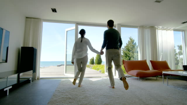 Happy Young Couple Holding Hands  Runs out of Their Home onto the Terrace with the Seaside View. Happy Young Couple Holding Hands  Runs out of Their Home onto the Terrace with the Seaside View. modern house stock videos & royalty-free footage