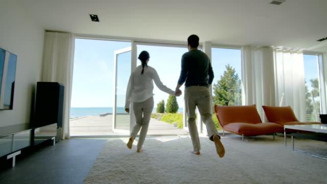 vídeos y material grabado en eventos de stock de feliz joven pareja sosteniendo manos corre fuera de su casa a la terraza con la vista de la playa. - nueva casa