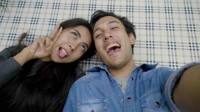 vidéos et rushes de heureux jeune couple tenant selfie smartphone prise et profiter d'une journée ensoleillée en dehors - photophone