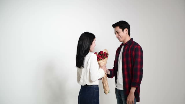 Happy young couple in love with bouquet of rose flower