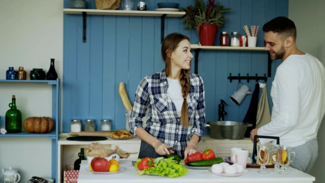 Heureux jeune couple dans la cuisine. Jolie femme dansante, cuisson et nourrir son petit ami dans la matinée - Vidéo