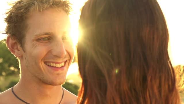 slow motion: happy young couple kissing at golden sunset - djurarm bildbanksvideor och videomaterial från bakom kulisserna