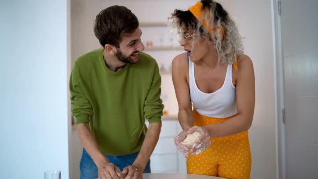 happy ungt par knådning degen tillsammans - videor med baka bildbanksvideor och videomaterial från bakom kulisserna