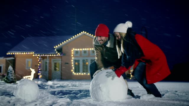 happy young couple makes a snowman, both rolling big snowball. family having fun on one winter evening. in the background house decorated with garlands. - estonia filmów i materiałów b-roll