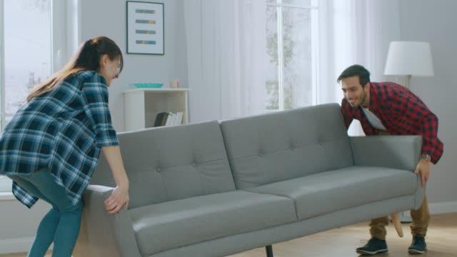 vídeos de stock, filmes e b-roll de feliz jovem casal move novo sofá para sala de estar, cair nele para o resto. apartamento moderno e luminoso com mobiliário elegante. - mobília