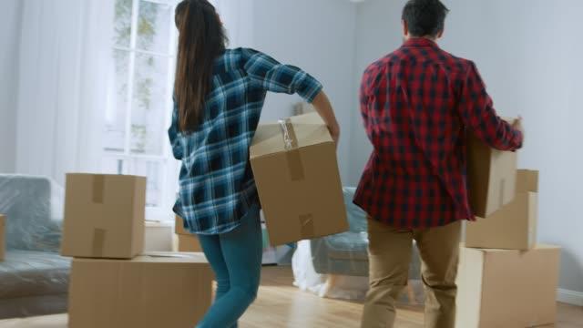 幸せな若いカップルの新しいアパートに移動、運ぶ段ボール箱もの、楽しい時を過すにハイファイブを与えます。若い彼氏と彼女は、一緒に暮らしている、ものを解凍を開始します。 - 荷物をとく点の映像素材/bロール