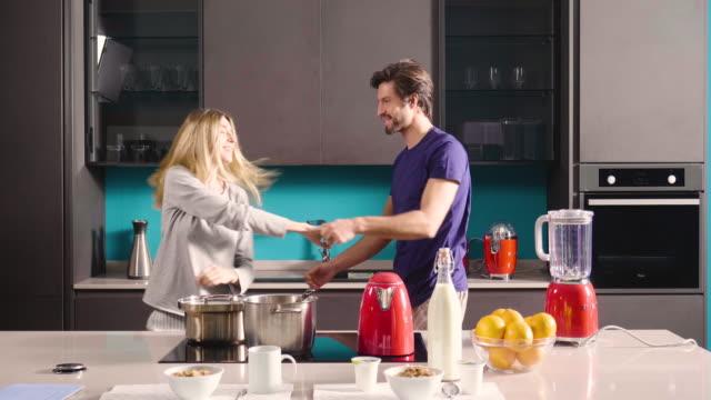 felice giovane coppia appena sposata ballando ascoltando musica in cucina indossando pigiama caffè mattina a casa in amore divertendosi. - romanticismo concetto video stock e b–roll