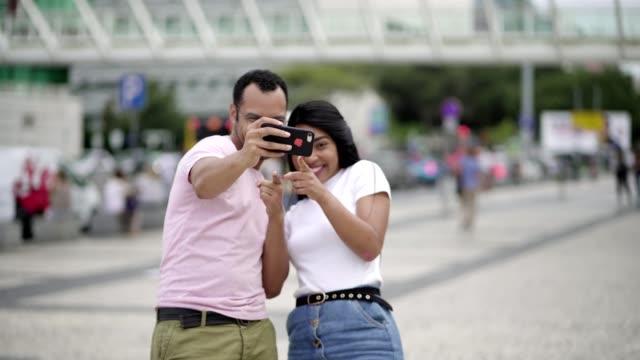 happy young couple posing for self portrait on square - fare la lingua video stock e b–roll