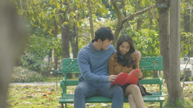 happy young couple reading a book together while sitting on a park bench. - two students together asian video stock e b–roll