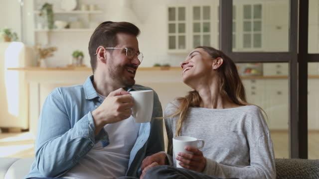 vídeos y material grabado en eventos de stock de feliz pareja joven relajándose hablando riendo bebiendo té de café - café bebida