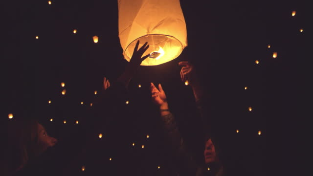 Happy young couple releasing flaming lantern at festival at night Happy young millennial couple holding flaming fire lantern at night during giant lantern festival outside lantern stock videos & royalty-free footage