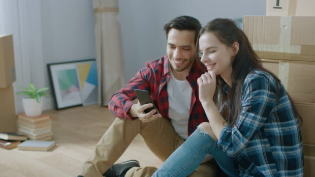 happy young couple sitting on the floor of the newly rented / purchased apartment use smartphone. unpacked cardboard boxes and covered furniture in the modern bright sweet home. - owner laptop smartphone video stock e b–roll