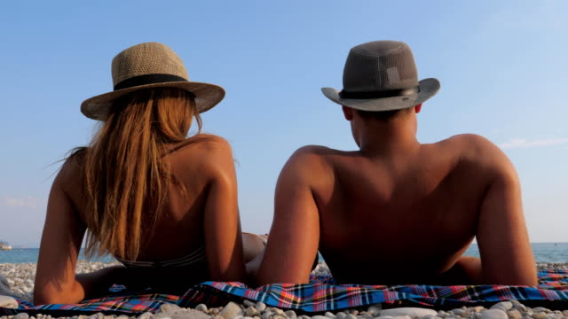 Happy Young Couple Sunbathing On Beach At The Seaside, Lying Down On The Back Happy young couple in hats, sunbathing on the beach with a pebbly coastline, lying on a blanket and looking into the distance. View from the back. Relax in the summer on the Mediterranean coast. 4K sunbathing stock videos & royalty-free footage