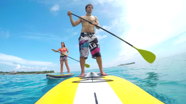 Happy young couple SUP boarding on blue ocean in Maldives video