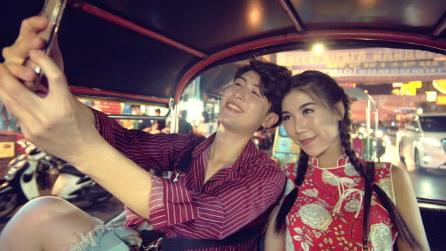 Happy young couple taking selfie portrait on Tuk Tuk Taxi in Bangkok city.