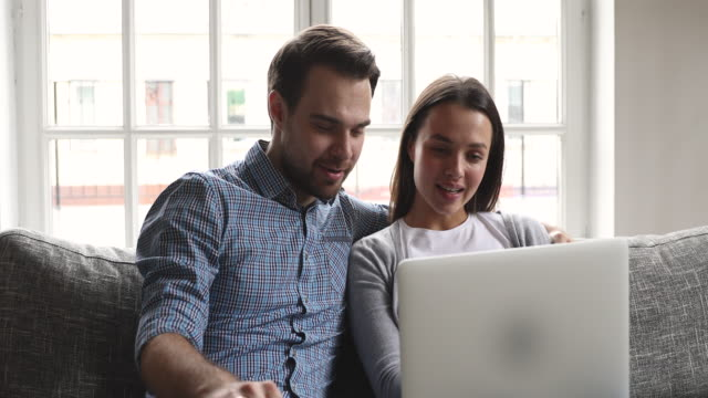happy young couple talking bonding using laptop sit on sofa - due genitori video stock e b–roll