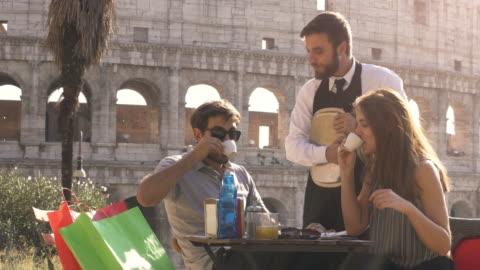 vidéos et rushes de heureux jeune couple de touristes dégustation café chat avec funny garçon élégant italien assis au bar restaurant en face du colisée à rome, au coucher du soleil de plaisanter et de rire s'amuser - italie