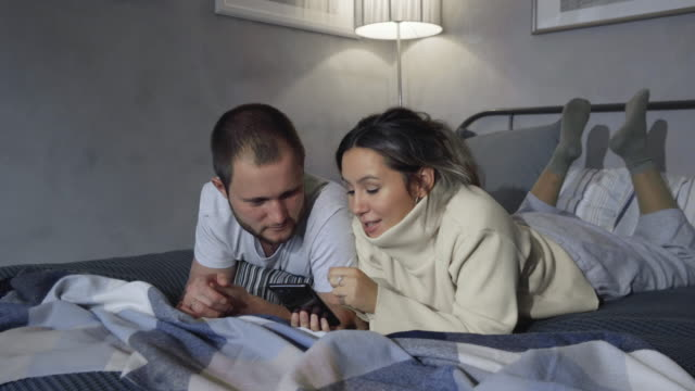 Happy Young Couple Use Smartphone in Bed at Night, They Share Screen, Browsing Through Social Networks, Sharing Pictures, Using Internet and Having Fun.
