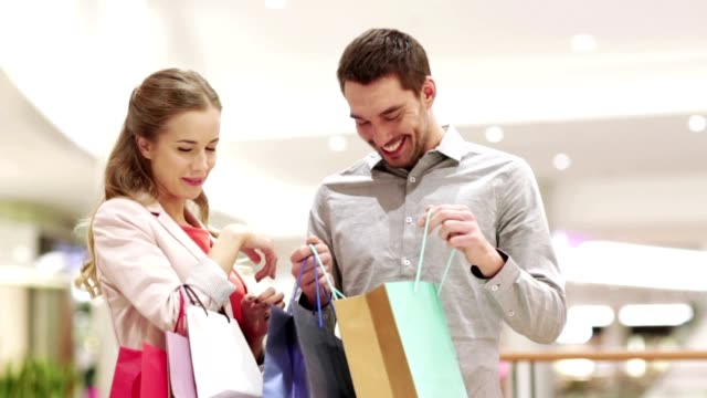 happy young couple with shopping bags in mall video