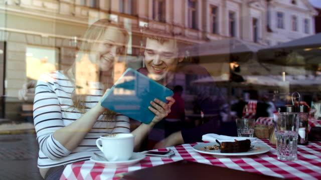 vídeos de stock e filmes b-roll de casal jovem feliz com tablet pc em um café - bar local de entretenimento