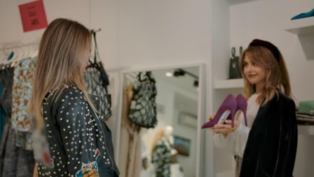 vídeos de stock, filmes e b-roll de clientes jovens felizes escolhendo sapatos enquanto compram em boutique moderna - boutique