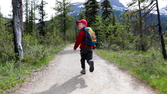 Happy Young Cute Redhead Boy Running on Trail at Emerald Lake in Summer