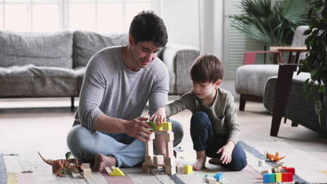 felice giovane papà e figlio bambino costruzione torre a casa - figlio maschio video stock e b–roll